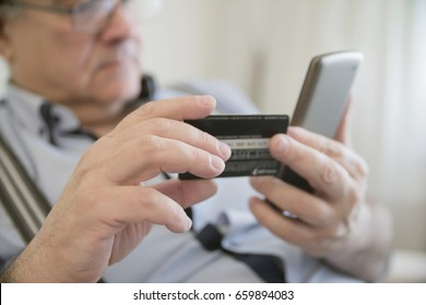 close-up adult gray-haired man holding a credit card and phone, it makes electronic payment