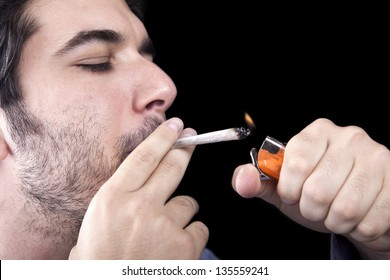 Closeup of an adult man (30 years old). He appears to be quite a bum, concentrated in lighting a marijuana jspliff (aka reefer; joint). Isolated on black background.