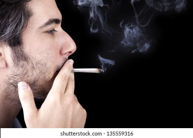 Closeup of an adult man (30 years old) with his profile to the camera. He appears to be quite a bum, concentrated in smoking a marijuana spliff (aka reefer; joint). Isolated on black background.