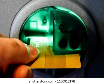 Close-up adult man's hand inserting a debit card into the slot of an automatic teller machine (ATM) enabling him to perform financial transactions