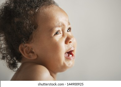 Closeup of African American baby crying isolated on colored background