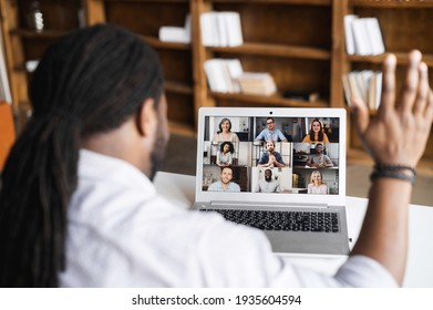 Close-up of African American man with dreadlocks using app for distance video communication with coworkers, friends, meeting online, looking and waving at laptop desktop with people profiles