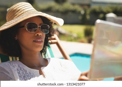 Close-up of African American woman with hat and sunglasses using digital tablet in her backyard on a sunny day