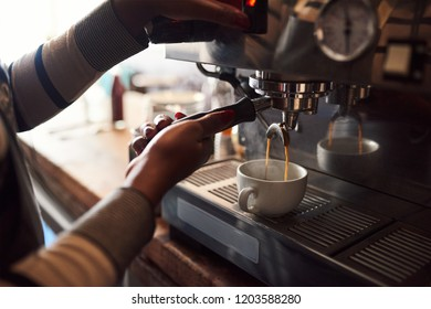 Closeup of an African barista making a fresh espresso while working behind the counter of her trendy cafe