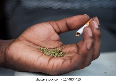 closeup of african man rolling a joint of cannabis in outdoor