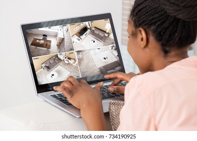Close-up Of African Woman Looking At Laptop Monitoring Video Footage At Home