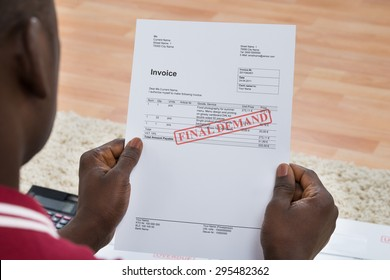Close-up Of African Young Man Holding Invoice With Final Demand Notification