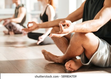 Closeup of african young man sitting and meditating in lotus pose with group