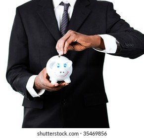 Close-up of an Afro-American businessman putting money in his piggybank