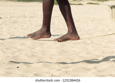 Closeup afro-american man feet walking on tightrope or slackline on sandy background. Slacklining is a practice in balance that uses nylon or polyester webbing tensioned between two anchor points.