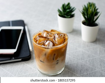 Close-up of the afternoon coffee. top view a glass of ice coffee with milk with tablet and smartphone on white table refreshing cold drink in the summer  modern lifestyle relaxing hour with copy space