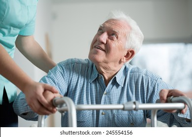 Close-up of aged man trying to stand up with walker