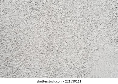 Close-up to an aged wall with irregular sprayed plaster
