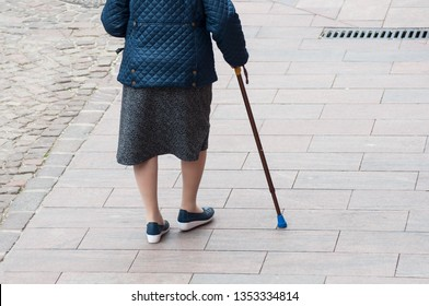 closeup of aged woman walking with stick in the street  on back view