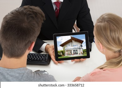 Close-up Of Agent Showing House On Digital Tablet To Couple At Desk