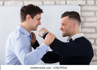 Close-up Of Aggressive Businessman Fighting With His Coworker In Office
