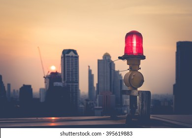 Closeup of an aircraft warning light on top of a highrise of building in evening time. for  safety concept