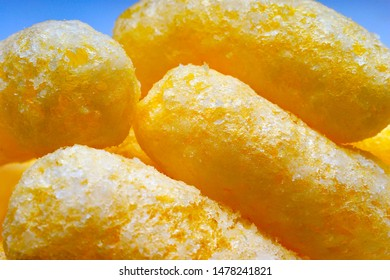 Close-up of Airy Crisps, Corn Puffs, Puffcorn Snacks on Blue Background. Crunchy Flavored Puffed Ready to Eat Treats. Party, Movie Theater, TV, Game Snacks Perfect for Sharing With Your Friends.