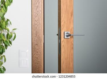 Close-up of ajar door. Steel door handle, dark textured wood. Element of modern interior