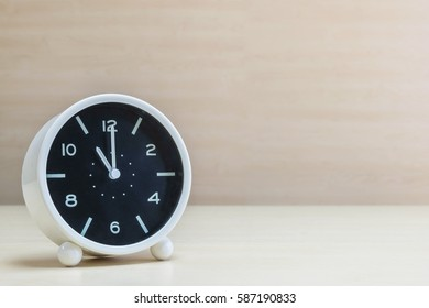 Closeup alarm clock for decorate in 11 o'clock on brown wood desk and wall textured background with copy space