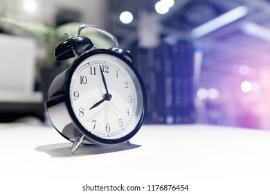 Closeup alarm clock for decorate in before 8 o'clock on wood desk.