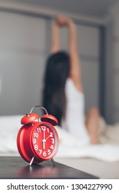 Closeup alarm clock having a good day with background happy woman stretching in bed after waking up
