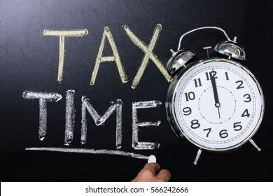 Close-up Of Alarm Clock Near Tax Time Concept On Blackboard