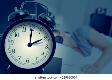 closeup of an alarm clock on a nightstand adjusting backward one hour at the end of the summer time, while a young man sleeps in bed
