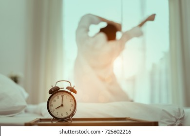 Closeup alarm clock,Asian woman stretching wake up in the morning and sitting on bed at window door side relaxing in holiday with sunlight, Vintage