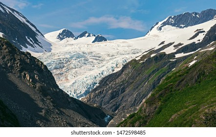 closeup of an alaskan glacier near portage and whittier surrounded by mountains with blue sky and puffy clouds in the background