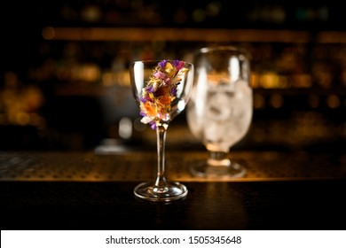Close-up of an alcohol cocktail with flower and glass with ice on a wooden and metal bar counter