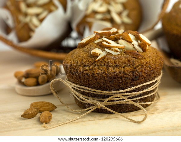 close-up of an almond muffin, on a wooden table, with a basket full of other muffins in the background