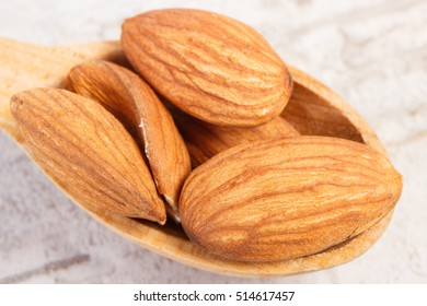 Closeup of almonds on wooden spoon lying on old rustic board, healthy nutrition