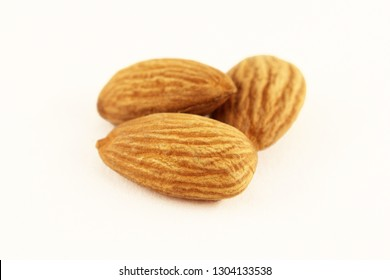 Closeup of almonds. Three almond nuts on a white background