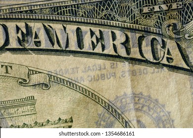 Close-up at America text, highly magnified surface of worn 5 dollars note with visible details of cotton fiber paper, with all flaws, watermarks and traces of usage.