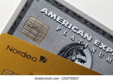 Closeup of American Express Platinum, MasterCard Gold by Nordea together. Symbols of wealth and modern financial business. Photographed in Kuopio, Finland during February 2019.