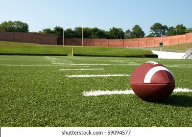 Closeup of American football on field with goal post in background