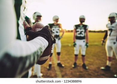 Closeup of an American football quarterback standing with his teammates during a practice session in the afternoon