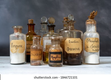 closeup of ancient apothecary pots with ingredients for medicine isolated over dark background. translation : terpine powder, Drosera and aubepine tincture, kola tincture, Iris essential oil, morphine