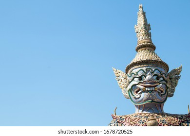 Closeup Ancient Head and face of Thai big giant statue with blue sky, Royal Grand Palace (Wat pha kaew),Copy space at the left, Bangkok in Thailand.