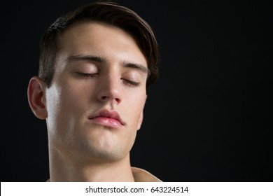 Close-up of androgynous man posing with his eyes closed