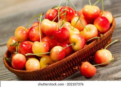 Closeup angled horizontal view of fresh Rainier cherries in basket on rustic wood