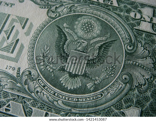 """Close-up Of Angled View Featuring """"E Pluribus Unum"""" In The Great Seal Of The United States Included In The Design On Back Of US One Dollar Bill"""