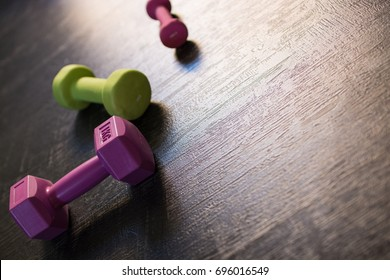 Closeup angled view image of a group of dumbbells for women aligned on a dark wooden floor background. Let's exercise. Copy space