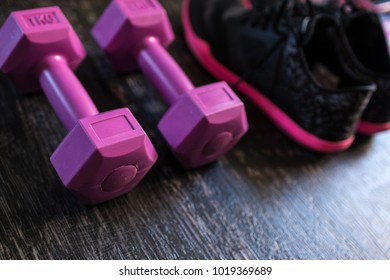 Closeup angled view shot of a pair of women sport shoes aside a pair of dumbbells aligned on a dark wooden floor background. Getting stronger with every training