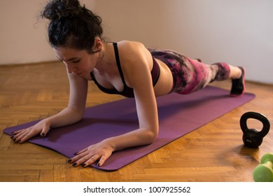 Closeup angled view shot of an young female athlete in a plank position at the gym. That plank is always a challenge