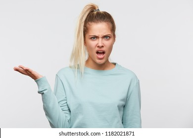Closeup of angry blonde young woman with ponytail wears blue sweatshirt feels irritated and holding copyspace on palm isolated over white background
