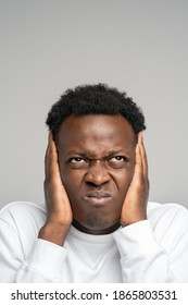 Closeup angry mad stressed afro man covering his ears and looking up, hears annoying loud noise from upstairs neighbors isolated on studio grey background. Fury, negative emotion.