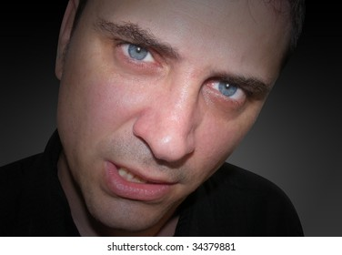 A closeup of an angry man's face. he looks mad, upset and frustrated. There are shadows around his face so the focus is in his eyes.