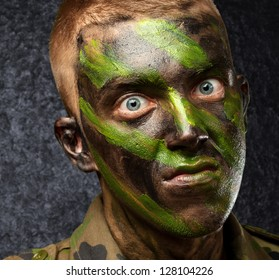 closeup of angry soldier with painting against a grunge background